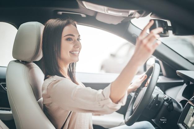 자신을 위한 한 순간. 차를 운전하는 동안 백미러를 보고 웃고 있는 매력적인 젊은 여성
