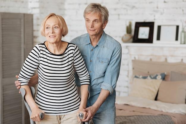 한 걸음 더. 그녀의 손을 잡고 그녀가 단단히 서 있는지 확인하여 그의 숙녀가 걷는 것을 돕는 달콤한 조심성있는 노인 신사