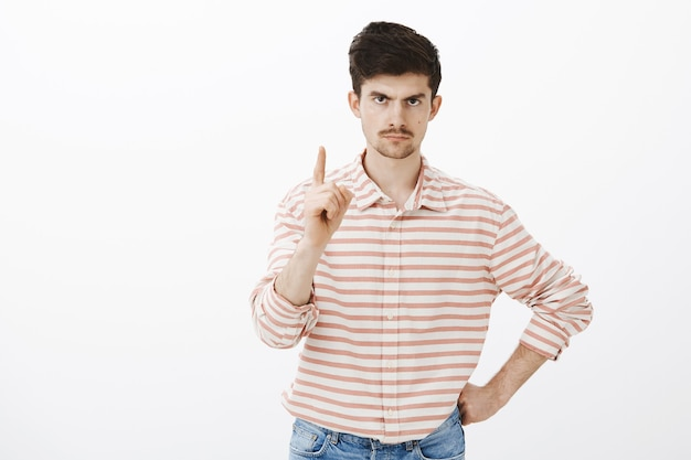 One more thing. indoor shot of displeased angry european man with moustache and beard, shaking index finger and frowning from displeasure and annoyance