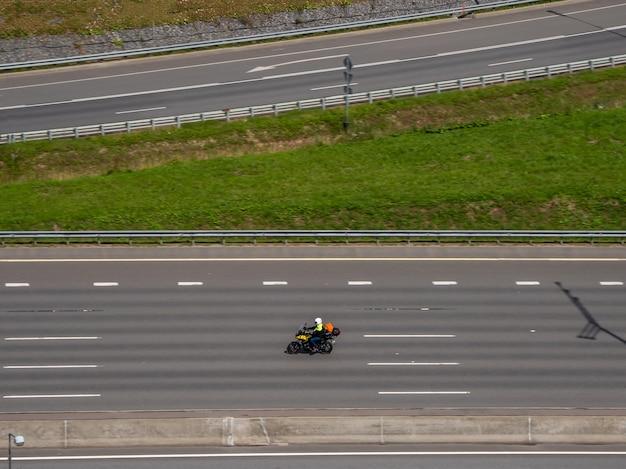 Один путешественник на мотоцикле мчится по автостраде, вид с воздуха. концепция единого путешествия.