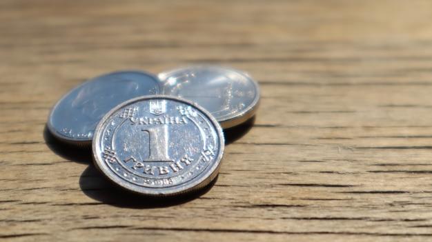 Одна новая монета гривна 2018 на деревянном фоне. украинские деньги