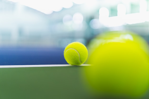 One new tennis ball on white line in blue and green hard court with blurred ball on right foreground