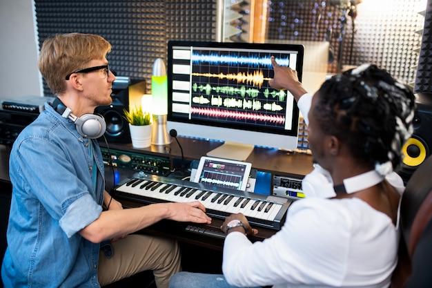 Один из современных музыкантов показывает форму волны на экране компьютера, объясняя ему, как микшировать звуки.