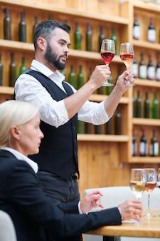 얼굴 앞에서 와인 두 잔을 들고 색을 비교하는 현대 소믈리에 중 한 명