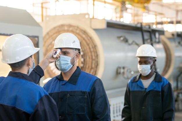 대형 작업장에서 동료나 부하 직원의 체온을 측정하는 온도계를 가진 여러 공장 노동자 중 한 명