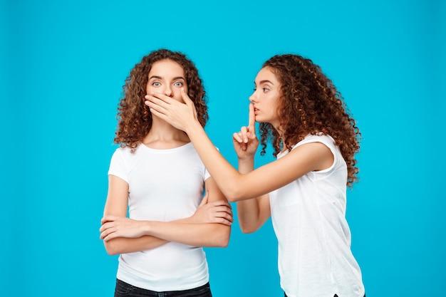 Одна из сестер-близнецов показывает молчание над синим.