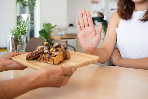 ヘルスケアの女の子の1人は、手を使ってチョコレートケーキのプレートを押しました。トランス脂肪を含む食品の摂取を拒否します。