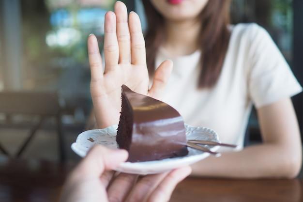 ヘルスケアの女の子の一人がチョコレートケーキのプレートを押すために手を使った。