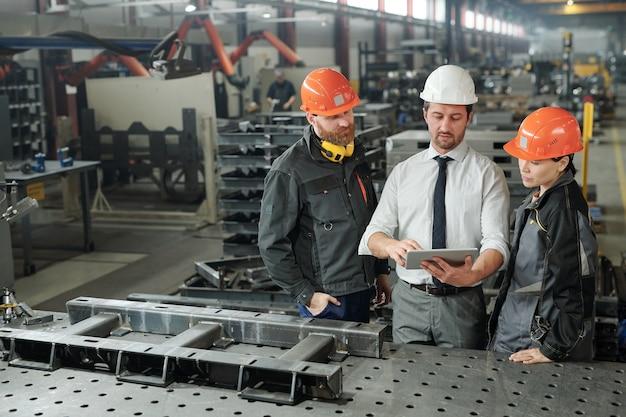 세 명의 엔지니어 중 한 명은 동료 온라인 데이터를 태블릿으로 보여주고 워크숍에서 새 프로젝트의 세부 사항을 설명합니다.