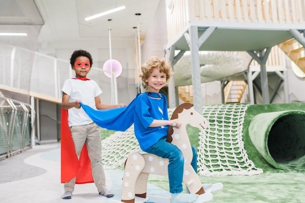 Один из двух симпатичных маленьких супергероев катается на игрушечной лошадке, а его африканский друг стоит рядом в игровом центре