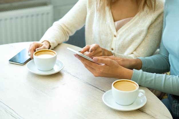 カフェでコーヒーを飲みながら友人とオンライン商品について話しているときにスマートフォンの画面を指している2人の若い現代女性の1人