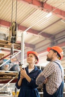 Один из двух молодых инженеров, тестирующих новое промышленное оборудование в цехе крупного завода