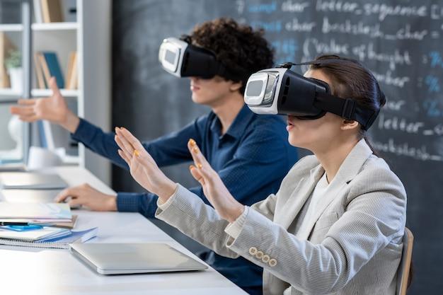 Один из двух молодых студентов в гарнитурах vr, касающийся виртуального дисплея во время презентации или участия в конференции