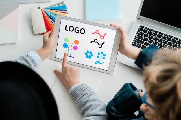 机で話し合っているときにタッチパッド画面のロゴ要素を指している2人の若い生徒の1人