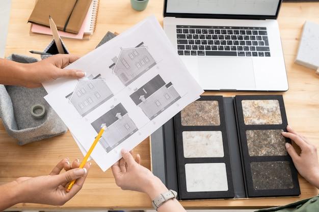 彼女の同僚がそれらの1つを指している間家のスケッチで紙を保持している若い女性デザイナーまたは建築家の1人