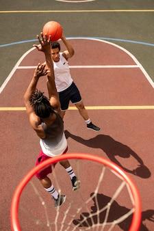 Один из молодых межкультурных баскетболистов атакует мяч, а его соперник собирается его бросить