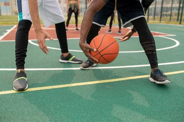 スポーツコートでボールを保持しながらボールを奪う若い異文化バスケットボール選手の1人