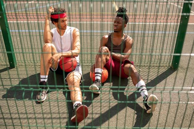 フェンスのそばで休憩中のゲームの詳細について友人またはプレイメイトに話している若い異文化バスケットボール選手の1人