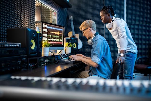그의 동료가 스튜디오에서 팀워크하는 동안 컴퓨터 화면을 보는 동안 피아노 보드 키를 누르는 젊은 이문화 음악가 중 한 명