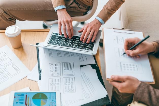 Один из молодых программистов или разработчиков программного обеспечения печатает на клавиатуре ноутбука, в то время как его коллега делает эскизы интерфейса