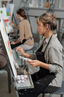 Один из юных студентов курса живописи сидит перед мольбертом и работает над неоконченной картиной на уроке.