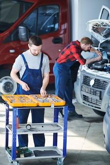 Один из молодых техников в спецодежде, выбирая ручные инструменты в ящике для инструментов