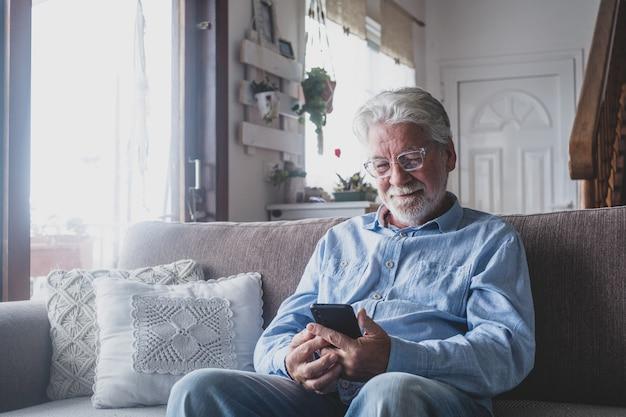 一人の老人が自宅で電話を使ってソファに座って笑顔で友達とチャットしたりネットサーフィンを楽しんだりしています。スマートフォンで屋内の男性シニアを満足。
