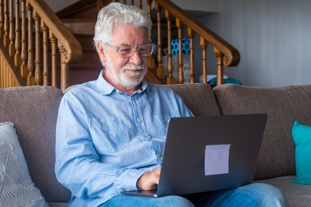 One old and mature man using laptop, working with computer sitting on the sofa at home indoor concept and business man lifestyle. male pensioner and retired person having fun relaxing on couch