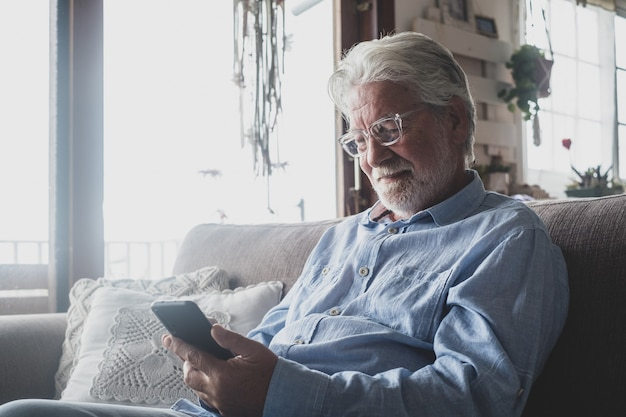 One old and mature man using phone, working with smartphone sitting on the sofa at home indoor concept and business man lifestyle. male pensioner and retired person having fun relaxing on couch