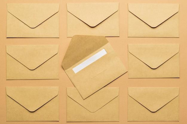 Один открытый почтовый конверт с листом бумаги на фоне нескольких закрытых конвертов. плоская планировка.
