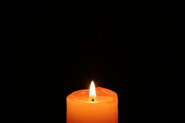 Одна оранжевая свеча, сияющая в темноте, со свободным пространством для текста или дизайна
