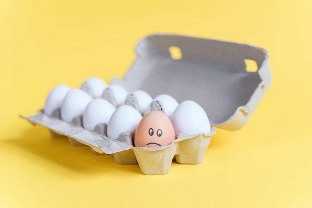 Одно оранжевое яйцо с нарисованным грустным лицом среди белых яиц в картонный лоток. отличается от других.