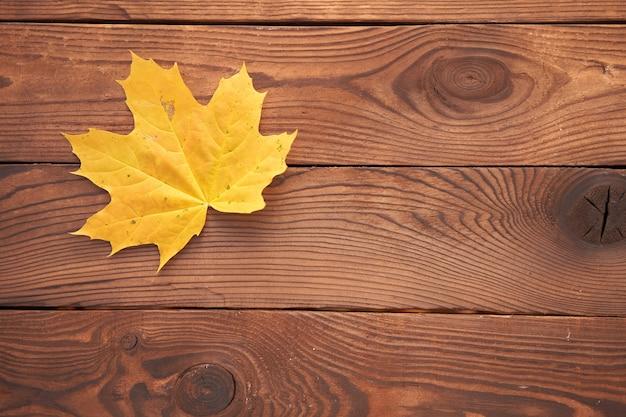 1つのオレンジ色のカエデの秋の葉は、ヴィンテージの木製の背景平面図季節概念にあります。秋が来ています