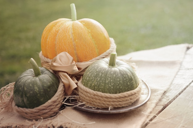 One orange pumpkin and two green pumpkin on the wooden table dec