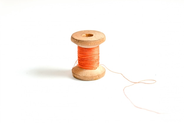One orange thread bobbin isolated on white background