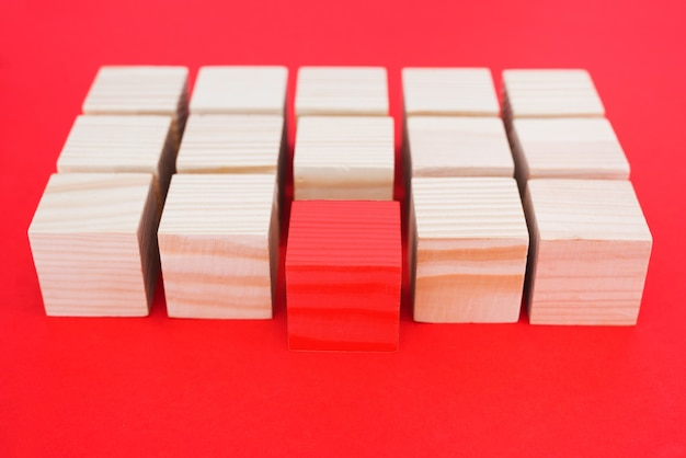 One other red cube block among wooden blocks on a red background. the concept of individuality, leadership and uniqueness