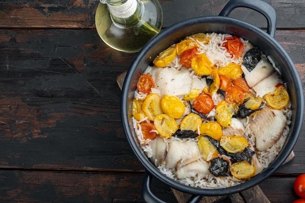Одна сковорода сказочной рыбы, с рисом басмати и помидорами черри, на старом деревянном столе, вид сверху с местом для текста