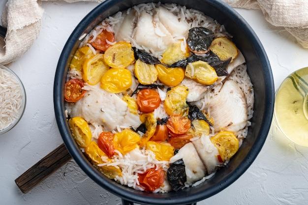 バスマティライスとチェリートマトを添えた素晴らしい魚1枚、白いテーブル、上面図