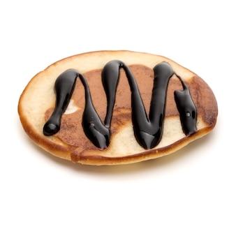 白い背景の切り欠きに分離されたチョコレートシロップと1つのパンケーキ。