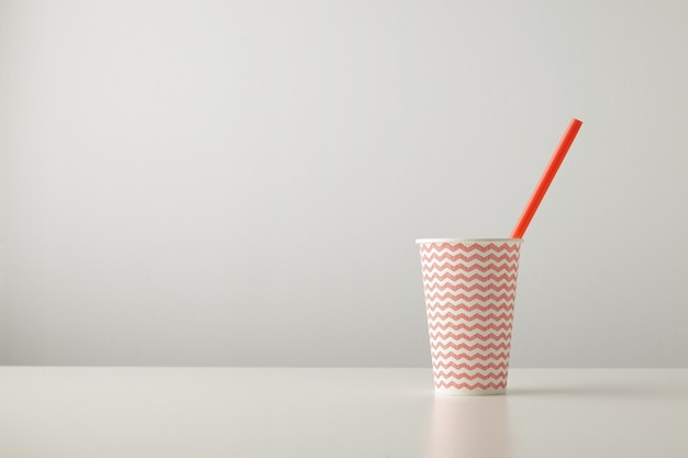 One paper cup decorated with red line pattern and with drinking straw inside isolated on white table