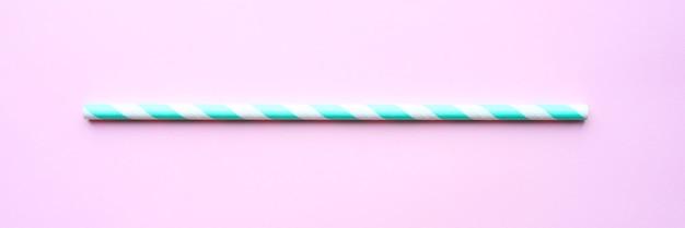 ピンクの背景のパーティーのための1つの紙の縞模様の白と緑のストロー。テキスト用のスペース。バナー