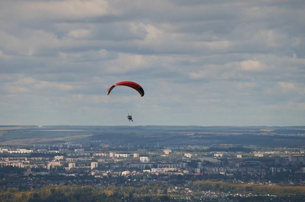 雲を背景に青い空を飛んでいるパラグライダーが1機。晴れた日に空をパラグライダー。
