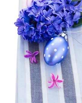 Одно пастельное голубое пасхальное яйцо с каймой из свежего гиацинта, изолированное на белом