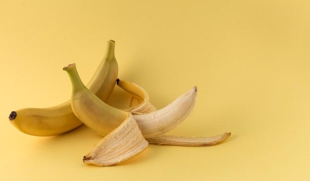 Один очищенный и один неочищенный желтый банан.