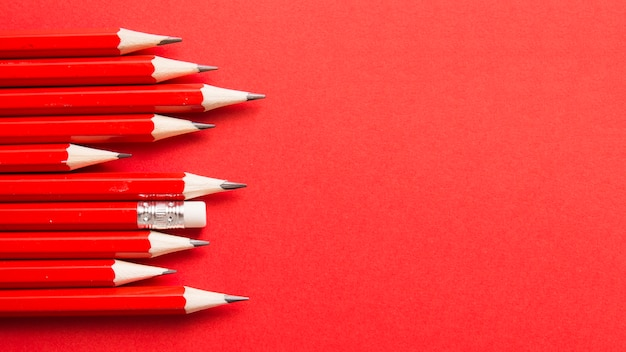 One pencil standing out from other sharp pencils on red backdrop