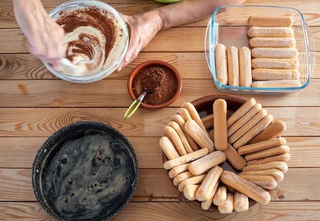 甘いティラミスを作るのに忙しい一人木製テーブルのすべての材料