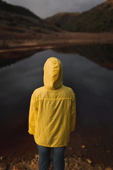 One person facing away of the camera with a yellow oilskin hoodie looking at a red river in spain.