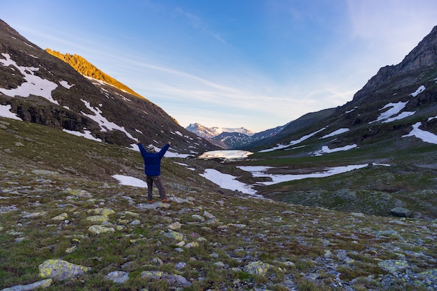 One person looking at colorful sunrise high up in the alps.