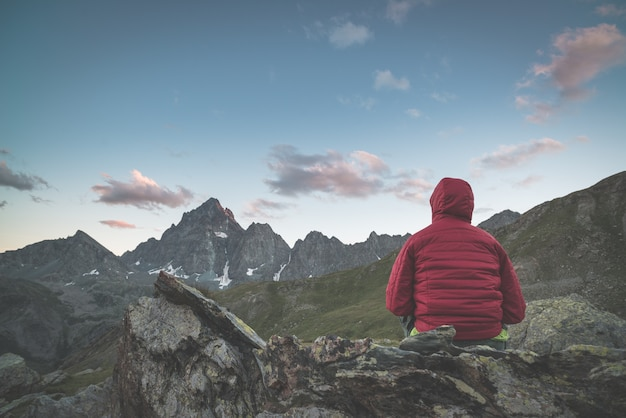 One person looking at the majestic view mountain peaks at sunset high up on the alps