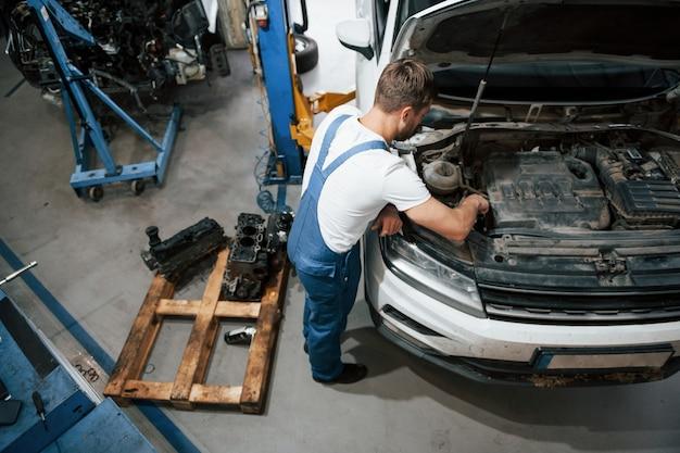 Только один человек. сотрудник в синей форме работает в автомобильном салоне.